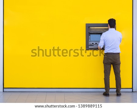 Man using a credit card in an atm for cash withdrawal #1389889115