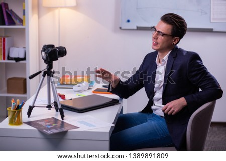 Active attentive guy. Narcissistic dark-haired businessman in clear glasses and dark jacket discussing problems on camera #1389891809