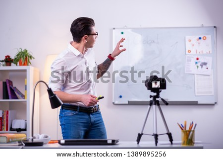 Professional science blogger. Expressive dark-haired man wearing neat white shirt and pointing on the desk with graphics #1389895256