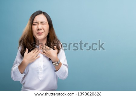 Woman has sore throat isolated over blue background #1390020626