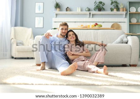 The happy couple in pajamas sitting on the floor background of the sofa in the living room. #1390032389
