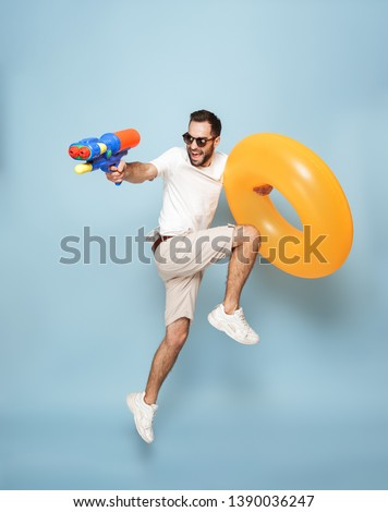 Full length of a cheerful excited man wearing blank t-shirt jumping isolated over blue background, having fun with inflatable ring and water gun #1390036247