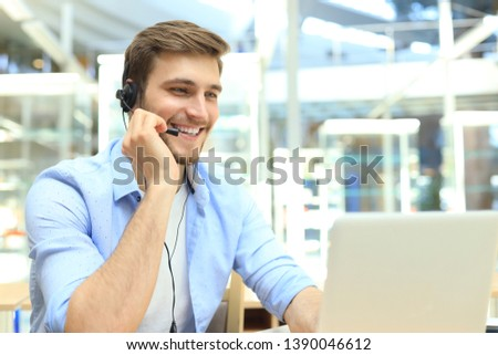 Happy young male customer support executive working in office. #1390046612