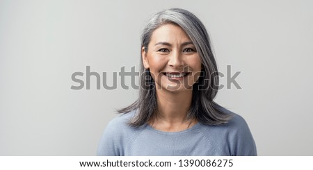 Beautiful Mature Asian Woman Smiles Broadly In Studio. Right Side Tonned Closed-Up Portrait. White Background.