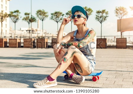 Young alternative girl skater wearing cap and sunglasses sitting on penny board on the city street looking up cool #1390105280