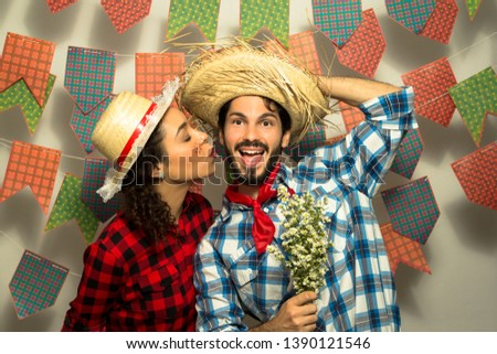 Festa Junina: party in Brazil in the month of june. Man and woman dressing checked pattern clothes. Pretty woman is kiising happy man. He is holding flowers. #1390121546