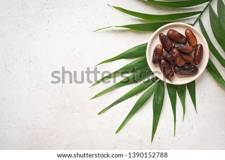 Dates fruits on plate on white background, top view, copy space. Organic dried dates fruits. Royalty-Free Stock Photo #1390152788