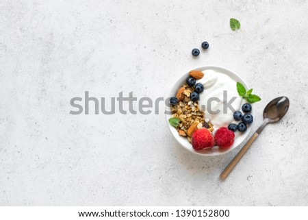 Granola with yogurt and berries for healthy breakfast. Bowl of greek yogurt with granola, almonds, blueberries and strawberries, top view, copy space. #1390152800