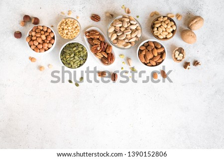 Various Nuts in  bowls on white background, top view, copy space. Nuts assortment frame - pecans, hazelnuts, walnuts, pistachios, almonds, pine nuts, peanuts, pumpkin seeds. #1390152806