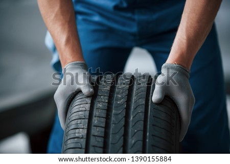 Dirt on the wheel. Mechanic holding a tire at the repair garage. Replacement of winter and summer tires. #1390155884