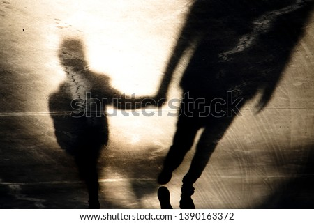 Blurry vintage shadow silhouettes of father and son walking hand in hand in old asphalt road  in sepia black and white  #1390163372