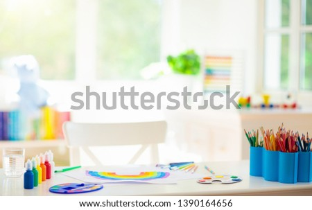 Kids painting in white bedroom at wooden desk. Arts and crafts supplies for school. Paint and drawing materials for children. White sunny room with big window for young child. Home interior for kid.  #1390164656