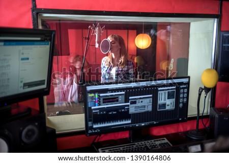 Female singer during vocal recording at music studio