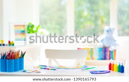 Kids painting in white bedroom at wooden desk. Arts and crafts supplies for school. Paint and drawing materials for children. White sunny room with big window for young child. Home interior for kid.  #1390165793