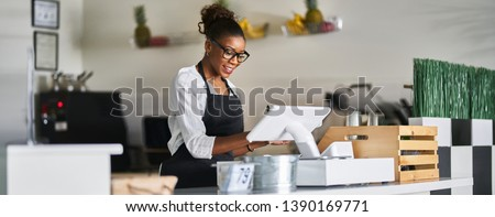 friendly african american shop assistant using pos terminal to input orders at restaurant #1390169771
