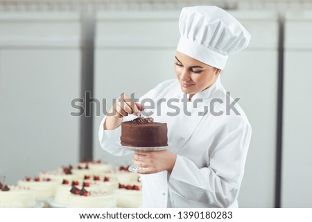 Confectioner decorating chocolate cake in pastry shop. #1390180283