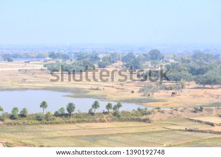 Natural rural landscape of India with a scenic pond, horizontal view in the villages of Deoghar, Santhal Pargana, Jharkhand, INDIA - Tourism concept with beautiful distant blue horizon.  Royalty-Free Stock Photo #1390192748