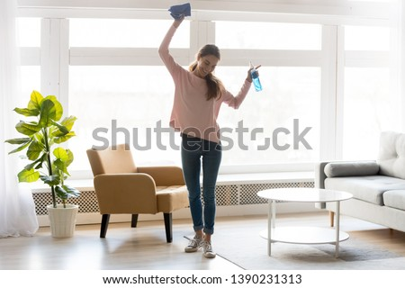Full-length woman in casual clothes dance do house cleaning holds blue rag spray bottle detergent feels happy, qualified housekeeping specialist agency hiring, quick fast and easy home chores concept #1390231313