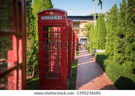 red telephone booth that is located in the park #1390236686
