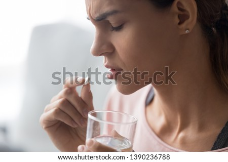 Unhappy woman side view holds tablet and glass of water close up image, abortion pill way end early pregnancy, unhealthy girl sad upset face expressions taking painkiller to reduce sharp ache concept #1390236788