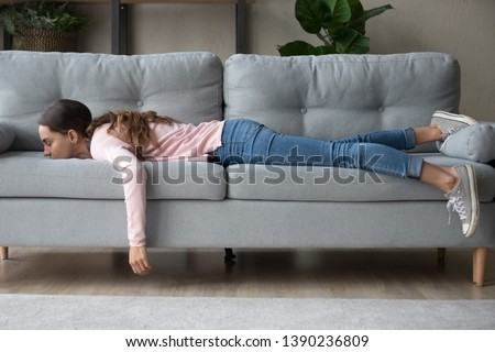 Full length of girl lying rest at home in living room buried her face in couch feels exhaustion having day nap lack of energy after party sleepless night or overworked, too tired no motivation concept