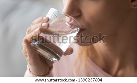 Close up cropped image thirsty woman holding glass drinks still water preventing dehydration, helps maintain normal bowel function and balance of body, skin and health care, healthy lifestyle concept #1390237604