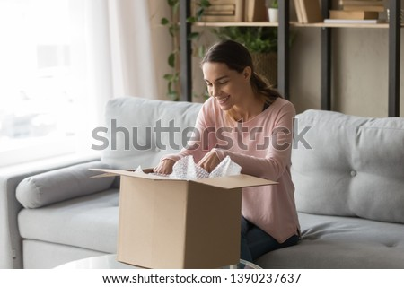 Happy woman sitting on couch at home opening carton box received parcel package from relatives or shopper make order internet website satisfied client, easy and fast service commerce delivery concept #1390237637