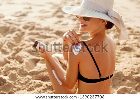 Beautiful Woman in Bikini Applying Sun Cream on Tanned  Shoulder. Sun Protection. Skin and Body Care. Girl Using Sunscreen to Skin. Portrait Of Female Holding Suntan Lotion and Moisturizing Sunblock. #1390237706