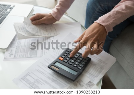 Close up cropped image coffee table full with papers invoices cheque bills, female hands holding receipt calculating company expenses results of incomes, bookkeeper accountant doing paperwork concept #1390238210