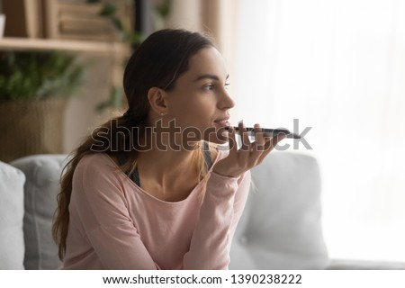 Woman sitting on couch holds phone talks on speakerphone with friend, makes voice recognition or request uses internet services through virtual assistant, record audio message, translator app concept #1390238222