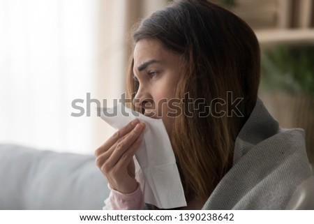 Side close up view woman covered with plaid sitting on couch holding paper tissue sneezing feels unhealthy suffers from seasonal allergy or grippe, illness caused by cold flat freezing at home concept #1390238642