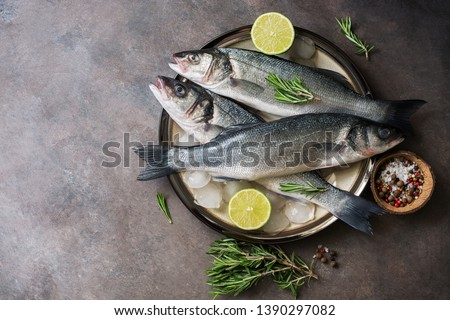 Flat lay fresh raw fish seabass in a plate with ice cubes, rosemary and lime on a dark rustic background. Top view, copy space Royalty-Free Stock Photo #1390297082