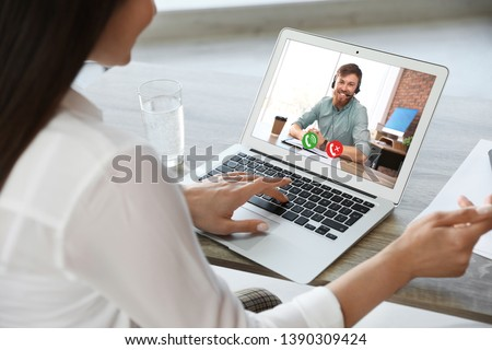 Woman having video chat with colleague at table in office, closeup #1390309424