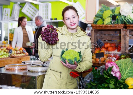 Portrait of smiling preteen girl in vegetable department of supermarket #1390314035