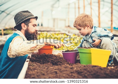 Side view father helping kid to plant flower with hand fork. Bearded man teaching his son gardening. Family and home education concepts. #1390321316