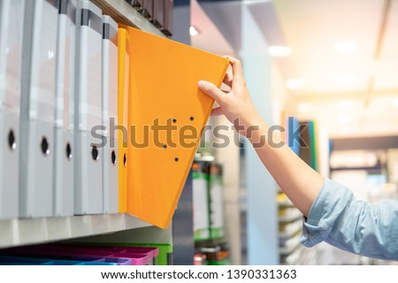Male hand choosing new orange ring binder file folder from colorful shelf display in stationery shop. Buying office supplies concept Royalty-Free Stock Photo #1390331363