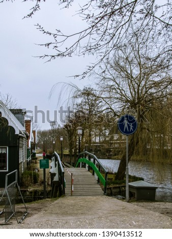 A bridge over a canal next to another channel with warning signs so they do not let go of children's hands. #1390413512