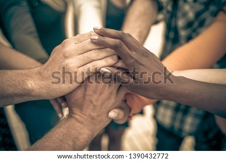 Young people putting their hands together. Friends with stack of hands showing unity and teamwork – Image Royalty-Free Stock Photo #1390432772