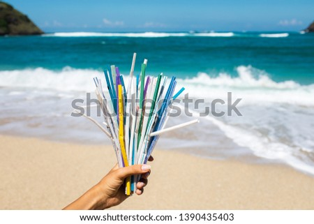 Hand holding heap of used plastic straws on background of clean beach and ocean waves. Plastic ocean pollution, environmental crisis. Say no plastic. Single-use plastic waste #1390435403