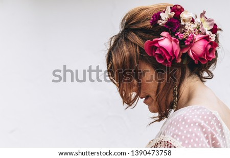 Beauty shot of a flamenco dancer with nice hairstyle and flowers in her hair on white background. April fair 2019 Seville #1390473758