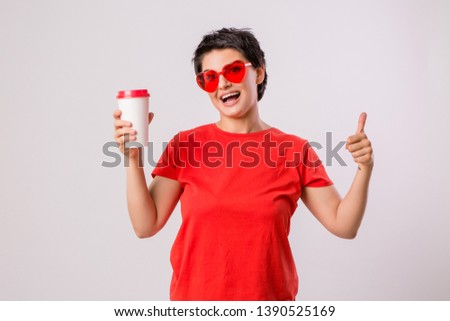 Close-up portrait of attractive pretty cute stylish cute cute cute funny brunette in everyday red t-shirt holding looking at paper Cup of coffee isolated on white background,concept of love for coffe #1390525169