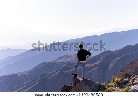 A young man in a blue jeans and dark sweater standing on side of rock at Key's View of Joshua Tree state park, California #1390680560