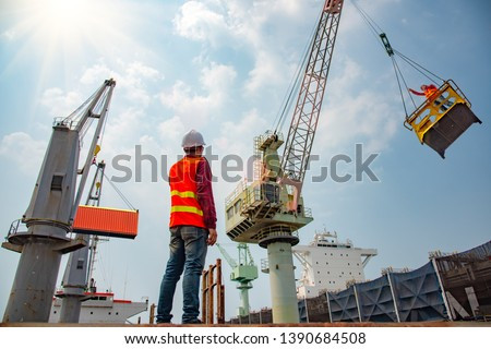 stevedore or foreman, engineering, loading master talks to crane driver by walkie talkie for safety lifting the goods shipment, lifting by gantry crane, working at risk on the high level insurance #1390684508