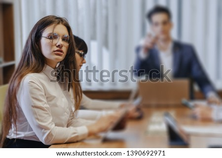 Stylish young different people in the modern office work at one desk with documents and a laptop #1390692971