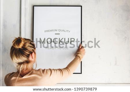 Blonde girl hanging a frame mockup