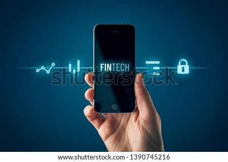 Fintech (financial technology) on smart phone concept. Hand with smart phone and text fintech and financial icons. #1390745216