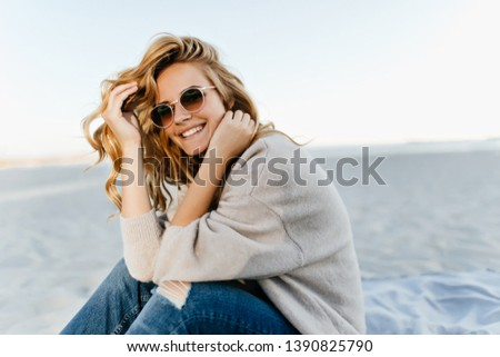 Debonair blonde girl sitting at sandy beach in autumn morning. Outdoor portrait of pretty curly woman smiling on sea background #1390825790