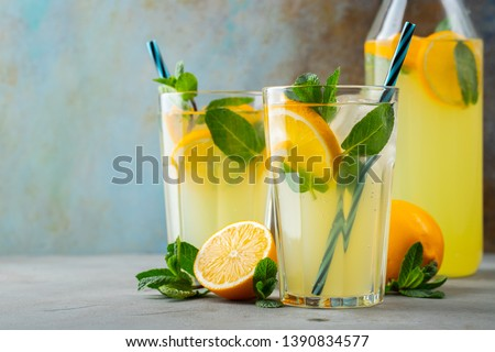 Two glass with lemonade or mojito cocktail with lemon and mint, cold refreshing drink or beverage with ice on rustic blue background. Copy space #1390834577