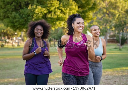Group of curvy girls friends jogging together at park. Beautiful smiling young women running at the park on a sunny day. Female runners listening to music while jogging. #1390862471