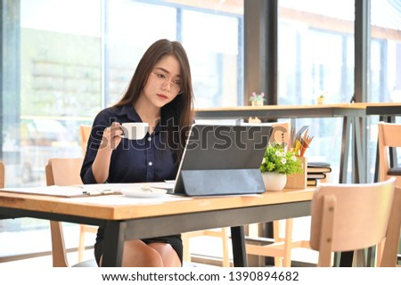Woman working in co working space with coffee cup on hands. #1390894682